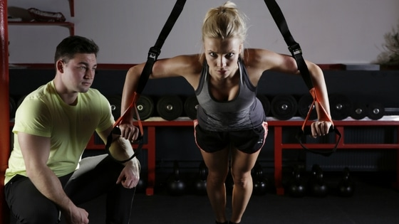 female client with fitness coach and using trx fitness